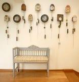 Silla de madera y muchos relojes del coocoo Foto de archivo