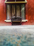 Silla de madera y ventana de madera roja de la pared de piedra Imagen de archivo