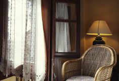 Silla de mimbre al lado de la ventana Imagenes de archivo