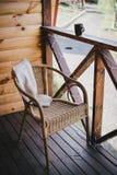 Silla de mimbre en un balcón acogedor Fotografía de archivo libre de regalías