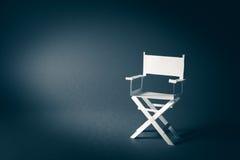 Silla de papel del director en un fondo gris azulado Imagenes de archivo