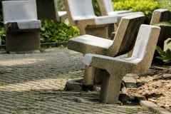 Silla de piedra vieja en el parque imagen de archivo