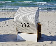 Silla de playa blanca con el número 112 Imágenes de archivo libres de regalías