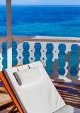 Silla de playa blanca en Gazebo con el fondo azul del océano fotos de archivo
