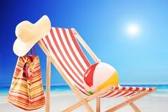 Silla de playa con la bola, el bolso y el sombrero por el mar Foto de archivo