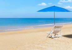 Silla de playa de madera blanca y parasol azul en la playa tropical Fotos de archivo libres de regalías
