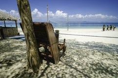 silla de playa de madera debajo de un árbol que hace frente a la agua de mar azul clara y a la playa arenosa blanca Cielo azul nu imágenes de archivo libres de regalías