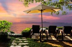 Silla de playa en el jardín en la puesta del sol Fotos de archivo libres de regalías