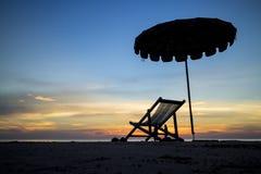 Silla de playa en puesta del sol Imagen de archivo libre de regalías