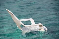 Silla de playa plástica blanca en el mar Foto de archivo