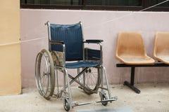 Silla de ruedas al lado de la pared foto de archivo