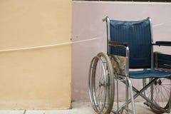 Silla de ruedas al lado de la pared fotos de archivo libres de regalías