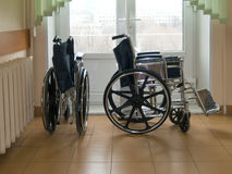 Silla de ruedas contra la ventana Imagenes de archivo