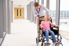 Silla de ruedas del doctor Pushing Girl In a lo largo del pasillo Fotografía de archivo libre de regalías