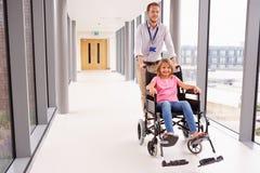 Silla de ruedas del doctor Pushing Girl In a lo largo del pasillo Foto de archivo