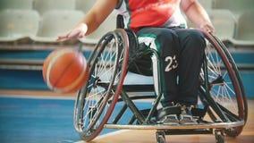 Silla de ruedas discapacitada, práctica del jugador de básquet que juega con la bola del tha en el pasillo de deporte almacen de metraje de vídeo