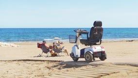 Silla de ruedas eléctrica en el fondo de la playa el mar almacen de metraje de vídeo
