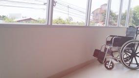 silla de ruedas parqueada en vestíbulo del hospital al lado de la ventana imagenes de archivo