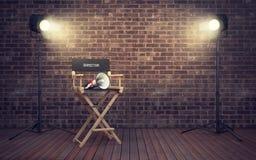 Silla del ` s del director de cine con el megáfono y los proyectores renderin 3D Fotos de archivo