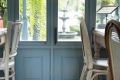 silla en café al lado de la ventana con la opinión del jardín Interior casero imagen de archivo