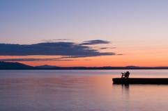 Silla en el extremo del embarcadero en el lago en la puesta del sol Imágenes de archivo libres de regalías
