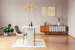 Silla en la tabla debajo de la lámpara del oro en interior de la sala de estar con el cartel sobre armario con la planta Foto ver foto de archivo