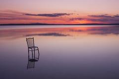 Silla en un lago en la puesta del sol con colores hermosos Imagen de archivo