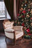 Silla lujosa en el interior Celebración del Año Nuevo Árbol de navidad adornado con juguetes y una guirnalda Imágenes de archivo libres de regalías