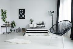 Silla negra diseñada en dormitorio moderno imagenes de archivo