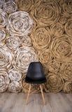 Silla negra en las piernas de madera en el piso cerca de la pared marrón, hal Foto de archivo libre de regalías