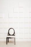 silla Negro-blanca cerca de la pared blanca en un estudio Fotos de archivo libres de regalías