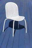 Silla plástica blanca sobre un piso de madera azul outdoor Foto de archivo libre de regalías