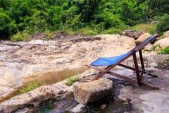 Silla plegable en la plataforma de piedra en la charca en parque Foto de archivo libre de regalías