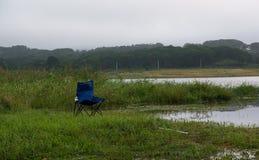 Silla que acampa en el lado del lago Fotografía de archivo libre de regalías