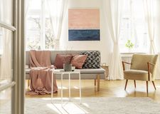 Silla retra de moda al lado del sofá gris elegante con las almohadas y la manta fotografía de archivo libre de regalías