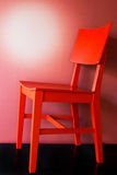 Silla roja que se coloca en un piso negro fotografía de archivo