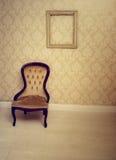 Silla tapizada antigüedad en un cuarto wallpapered Fotografía de archivo libre de regalías