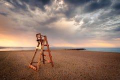 Silla vacía del salvavidas en la playa temprano en el día imagenes de archivo
