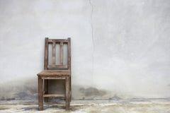 Silla vieja contra la pared vieja foto de archivo libre de regalías