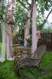 Silla vieja del vintage con los marcos y las flores románticos en hierba verde foto de archivo