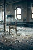 Silla vieja en una fábrica foto de archivo
