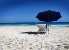 Silla y paraguas en la playa Imagenes de archivo