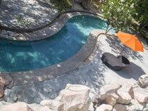 Silla y parasol de la piscina Fotografía de archivo