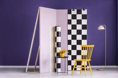 Silla y planta amarillas contra la pared del rosa en colores pastel con f a cuadros Fotos de archivo
