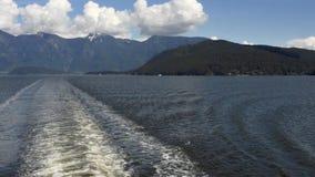Sillage de bateau et AVANT JÉSUS CHRIST de montagnes côtières, près de Vancouver, le Canada le jour d'été banque de vidéos