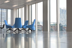 Sillas azules modernas en nueva oficina vacía por las ventanas Imagenes de archivo