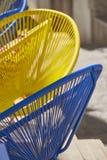 Sillas azules y amarillas en calle soleada fotos de archivo