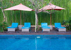 Sillas azules y piscina azul Fotos de archivo libres de regalías