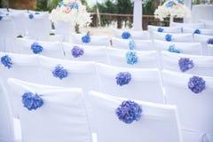 Sillas blancas adornadas con las flores hermosas en una ceremonia de boda Fotografía de archivo