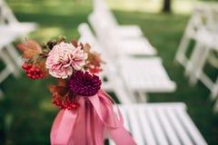 Sillas blancas adornadas con las flores púrpuras y rosadas Fotografía de archivo libre de regalías